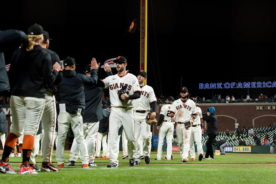 Giants players and coaches celebrate a win against the Cardinals.