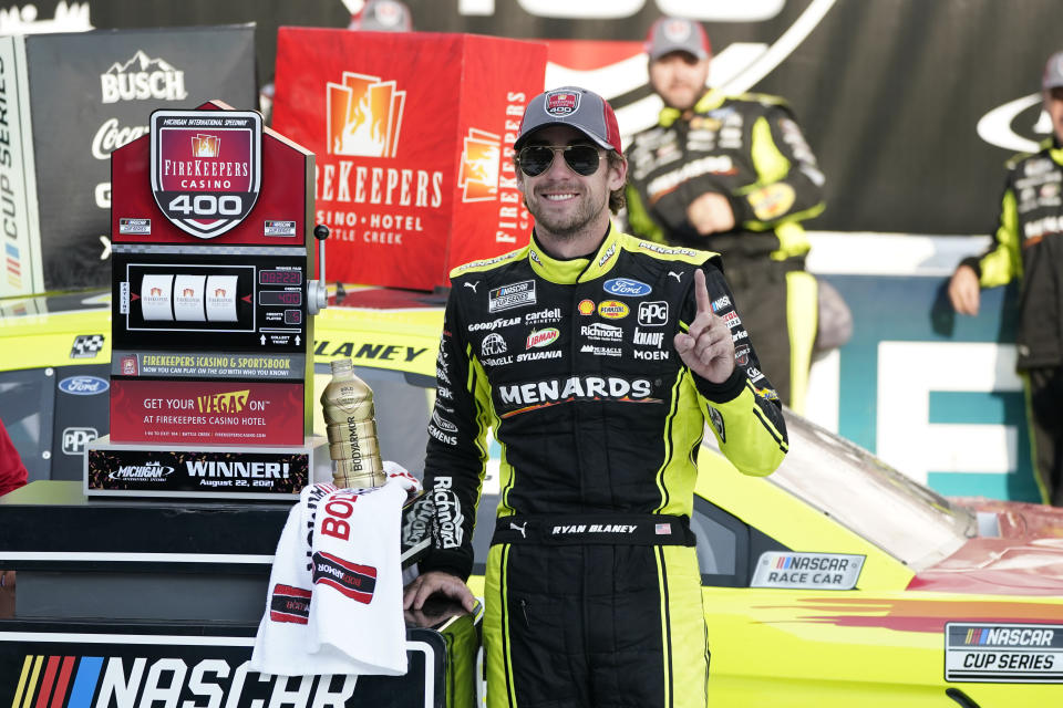 Ryan Blaney stands next to the winner's trophy after the NASCAR Cup Series auto race at Michigan International Speedway, Sunday, Aug. 22, 2021, in Brooklyn, Mich. (AP Photo/Carlos Osorio)