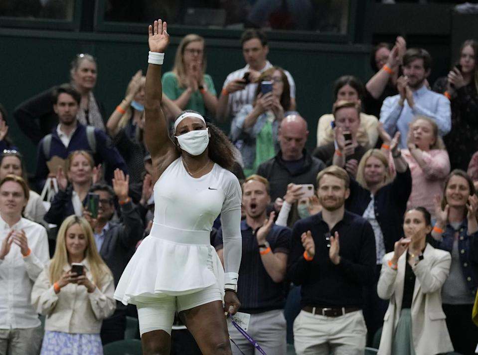 Serena Williams waves as she leaves the court.