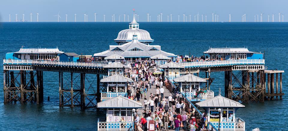 A view looking along Llandudno Pier on a busy summers day with the Wind Farm on the horizon beyond.