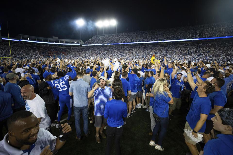 Kentucky fans flood the field after their team won an NCAA college football game against Florida in Lexington, Ky., Saturday, Oct. 2, 2021. (AP Photo/Michael Clubb)