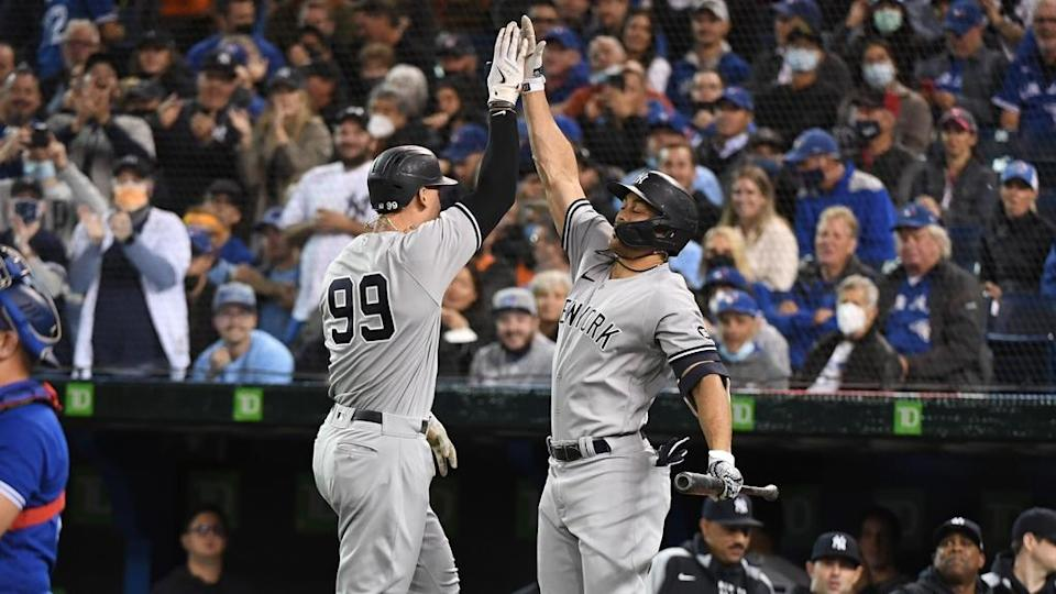 Sep 30, 2021; Toronto, Ontario, CAN; New York Yankees right fielder Aaron Judge (99) is greeted by left fielder Giancarlo Stanton (27) after hitting a solo home run against Toronto Blue Jays in the first inning at Rogers Centre.